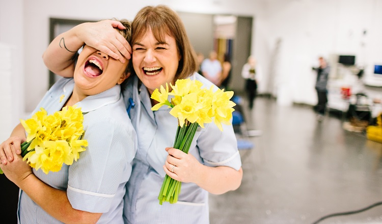 Marie Curie Nurses holding daffodils and laughing