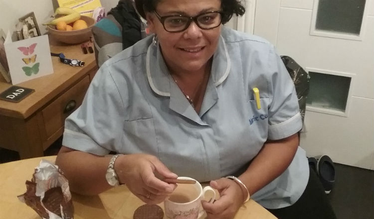 Nurse Annie enjoying a cup of coffee and a chocolate biscuit