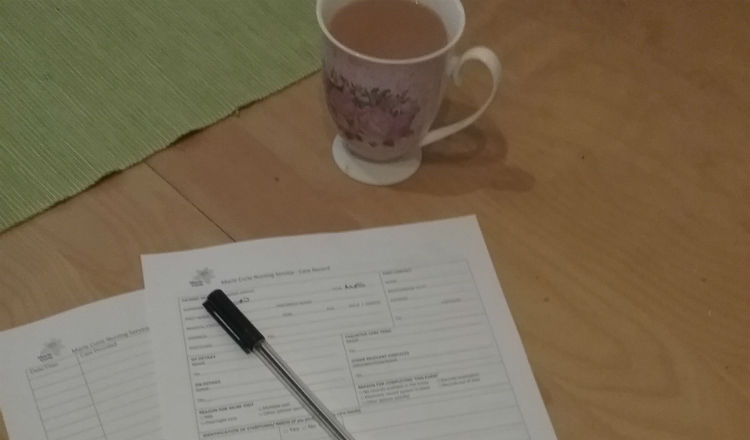 A cup of tea, forms and pen on a table top