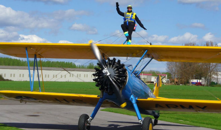 Chan stands on the wings of a plane completing her wing walk