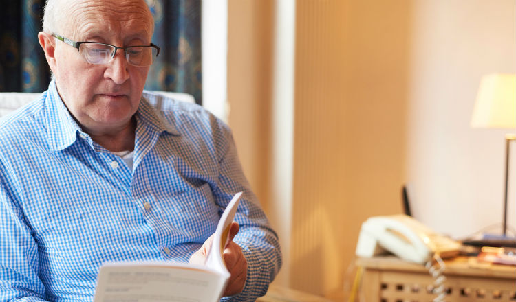 Older man sits and reads a Marie Curie information booklet in his living room