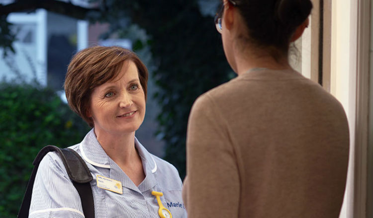 Marie Curie Nurse Paula greets a family member at a patient's house.
