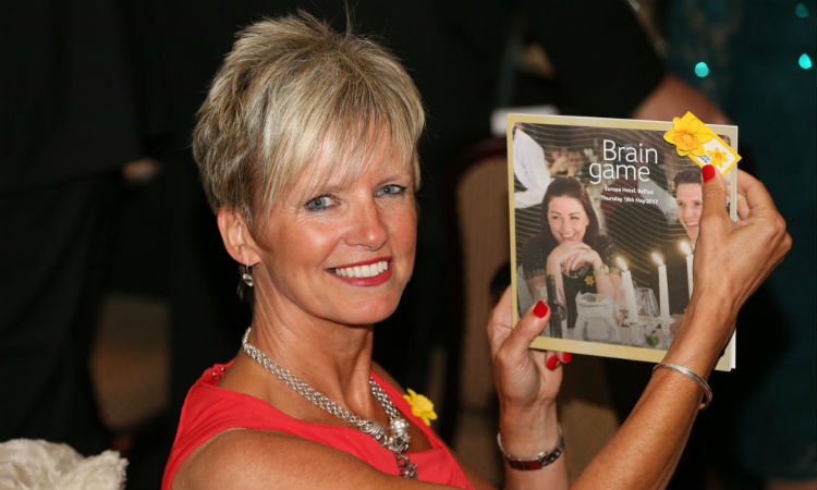 A Belfast Brain Game 2017 guest smiles as she holds up the programme