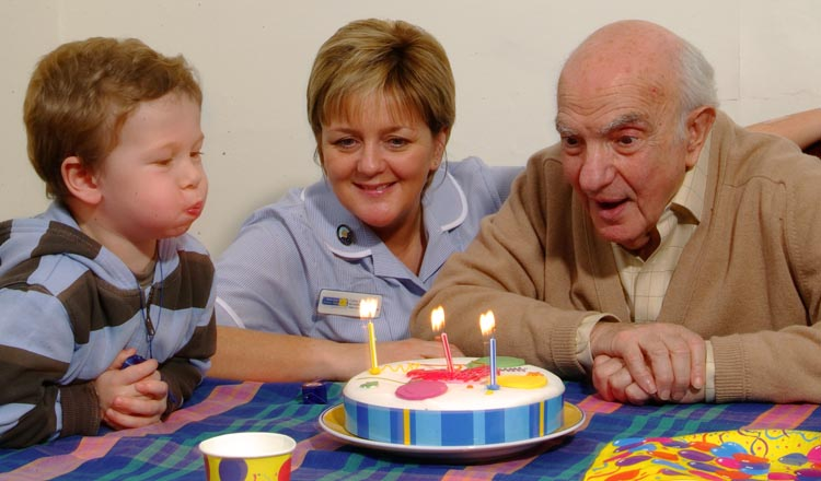 An elderly man helping his grandson blow out candles on a cake