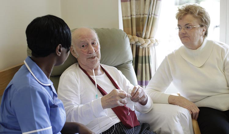 A nurse talking to an elderly couple
