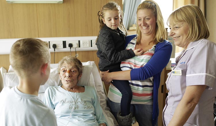 A hopice patient chatting to her grandson and surrounded by her family