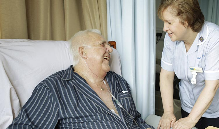 A man in bed laughing with his nurse