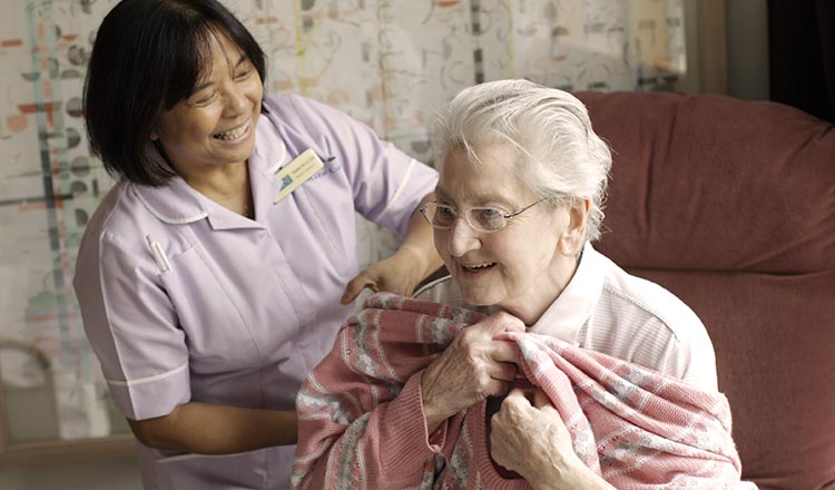 A nurse helping an elderly woman getting dressed